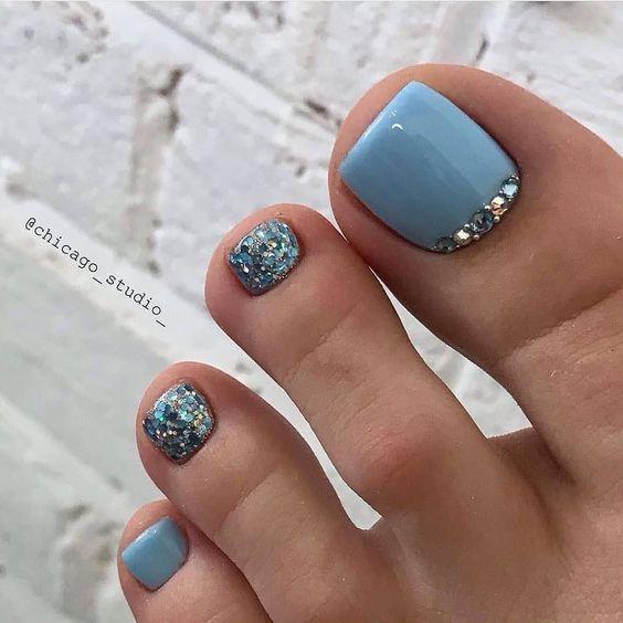 Niebieskie paznokcie u stóp z brokatem