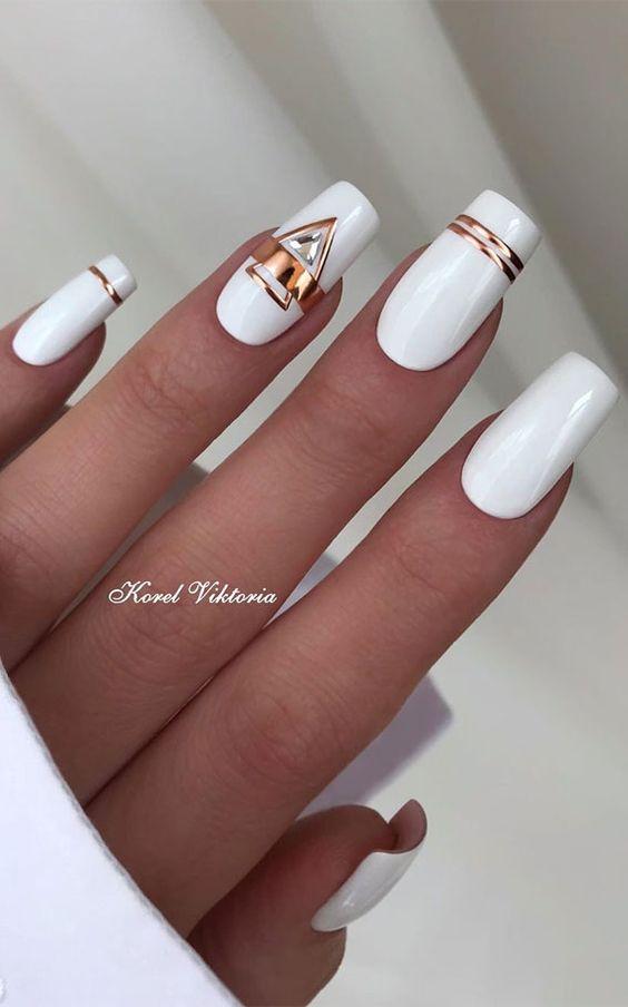 Białe paznokcie ze złotymi wzorkami