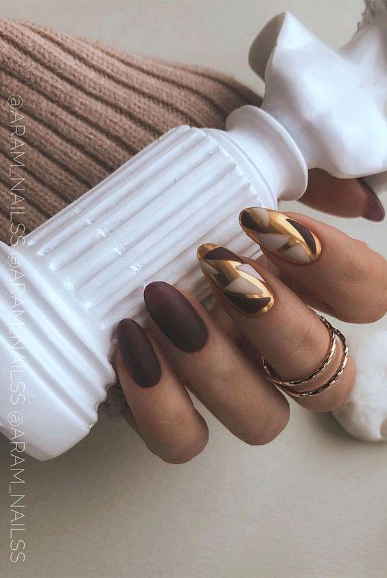 Brązowe paznokcie ze złotymi zdobieniami
